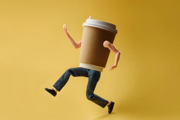 Bicchiere di carta per caffè o tè con braccia e gambe di bambola su una parete gialla.