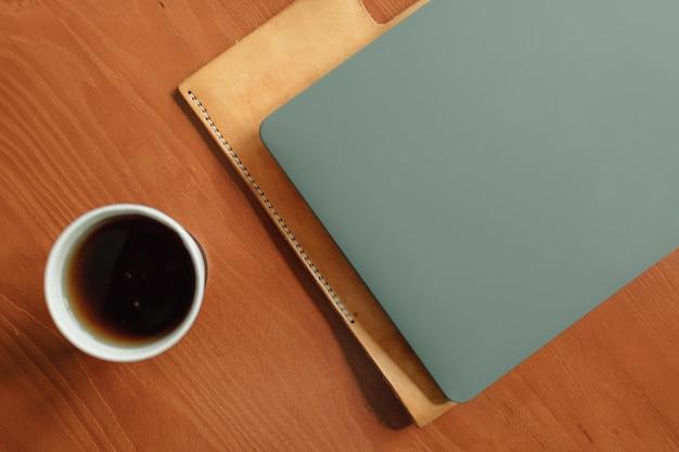 Bicchiere di carta di bevanda calda e laptop sul tavolo. concetto di lavoro da casa.