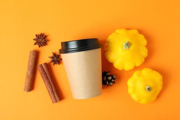 Bicchiere di carta e ingredienti per il latte di zucca su sfondo arancione