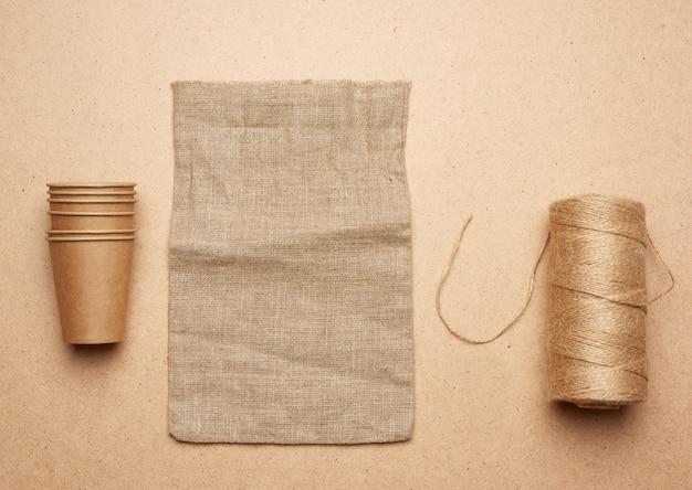 Bicchiere di carta, matassa con corda marrone e borsa vuota su un fondo di legno marrone