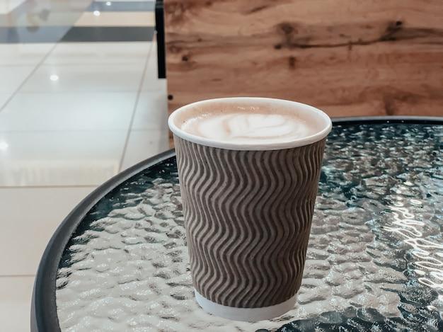 Bicchiere di carta con caffè su un tavolo di vetro in un bar. posto per il testo.