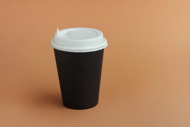 Bicchiere di carta con coperchio per caffè o bevande calde con te su uno sfondo marrone.