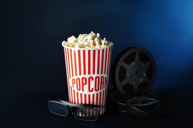 Bicchiere di carta con gustosi popcorn, bicchieri e bobina di film