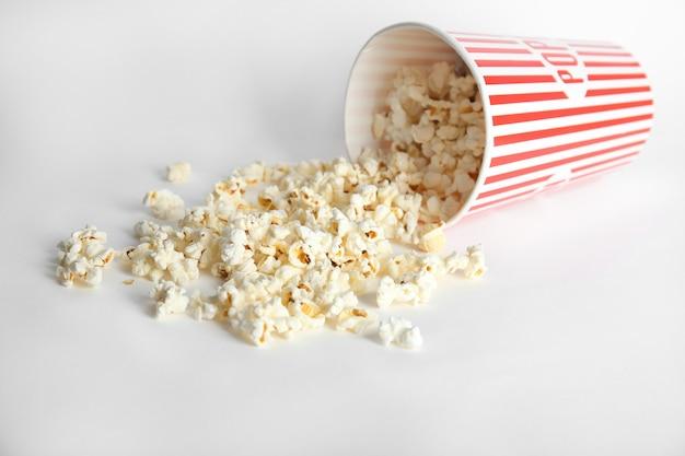 Bicchiere di carta con gustosi popcorn su bianco