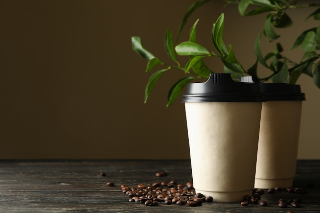 Bicchieri di carta, chicchi di caffè e pianta su legno