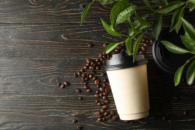 Bicchieri di carta, chicchi di caffè e pianta