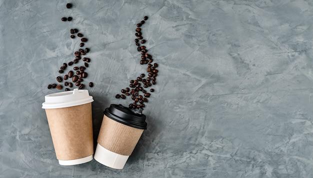 Bicchieri di carta per caffè, chicchi di caffè sotto forma di vapore che sale. parete neutra grigia, vista dall'alto con spazio di copia. caffè da asporto piatto o bevande calde. minimalismo