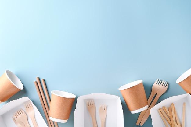 Bicchieri di carta, piatti, borsa, forchette in legno, cannucce, contenitori per fast food, posate in legno su sfondo azzurro. stoviglie in carta ecologica. riciclaggio e concetto di consegna del cibo. modello. vista dall'alto