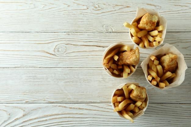 Bicchieri di carta con pesce fritto e patatine fritte su legno