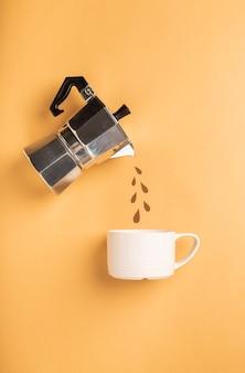 Carta tagliata gocce che versano da una caffettiera geyser in una tazza su carta marrone chiaro.