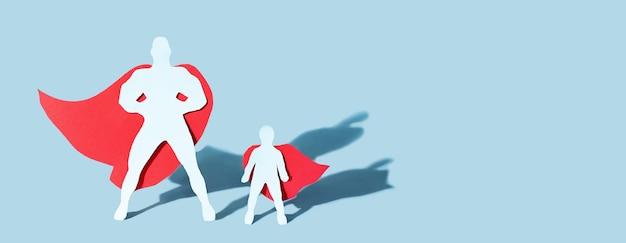 Figura di padre e figlio tagliati in carta che indossano mantelli da super eroe
