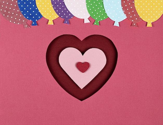 Carta tagliata a forma di cuore rosso e palloncini rosa.