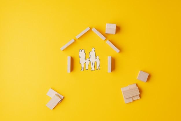 Sagoma di carta tagliata di una famiglia in casa fatta di blocchi di legno e pioli.