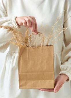 Borsa di carta ecologica con ramoscelli secchi di pianta organica naturale nelle mani di una donna, spazio per copie. concetto di eco naturale.