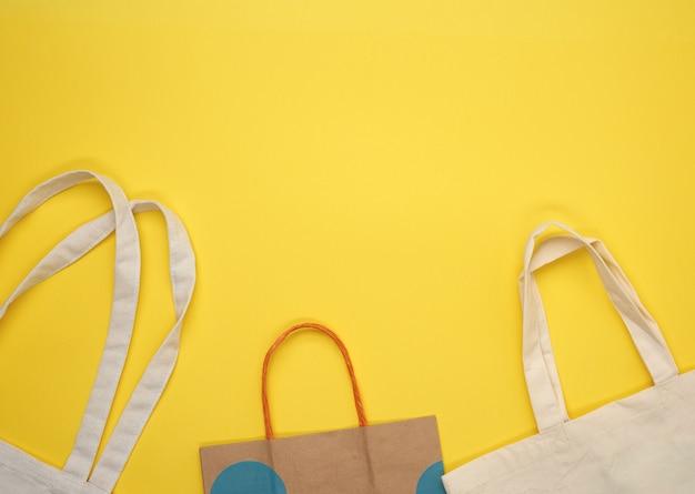 Carta e sacchetto di tessuto beige vuoto su sfondo giallo