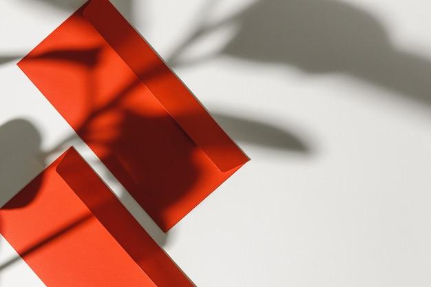 Busta di carta su fondo bianco con l'ombra della foglia, vista superiore