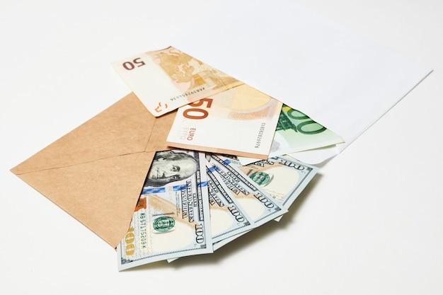 Busta di carta con soldi, primo piano. soldi del dollaro in una busta isolata su bianco. concetto di stipendio, guadagno e risparmio
