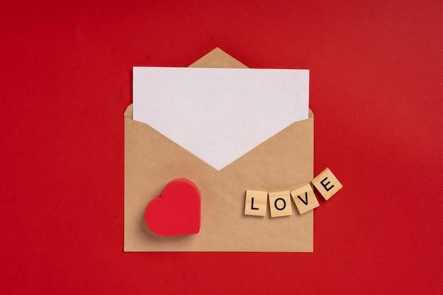 Busta di carta con un foglio bianco per il testo su uno sfondo rosso con cuori