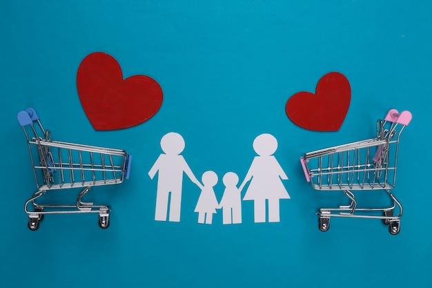 Famiglia di carta insieme, cuore e carrelli del supermercato sul blu. acquisto di famiglia.