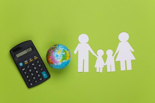 Famiglia di carta insieme al globo, calcolatrice su verde. concetto di ecologia, popolazione, famiglia, giornata della terra