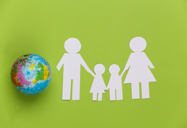 Famiglia di carta insieme al globo su verde. concetto di ecologia, popolazione, famiglia, giornata della terra. mondo nostra casa