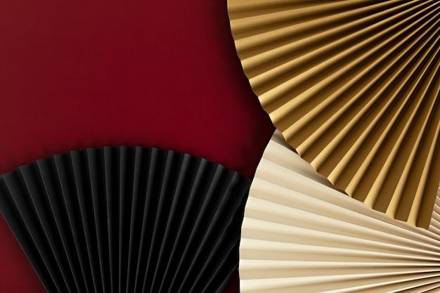 Ventagli di carta su sfondo rosso, capodanno cinese