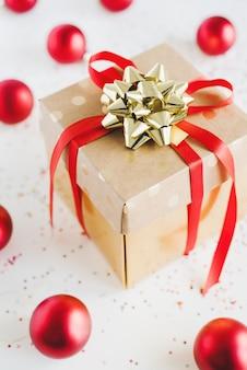 Confezione regalo di carta con nastro rosso e fiocco dorato, palle di natale rosse e coriandoli colorati su superficie bianca