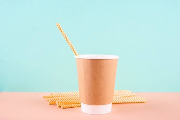 Bicchiere di carta con tubi per bere. utensili eco su uno sfondo chiaro.