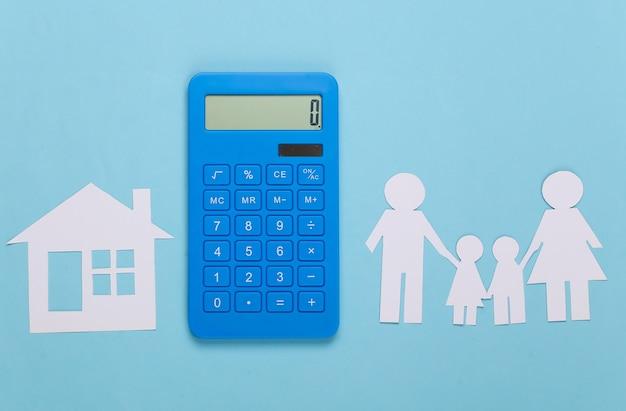 Famiglia felice di carta insieme alla casa, calcolatrice sull'azzurro. calcolo delle spese familiari, budget