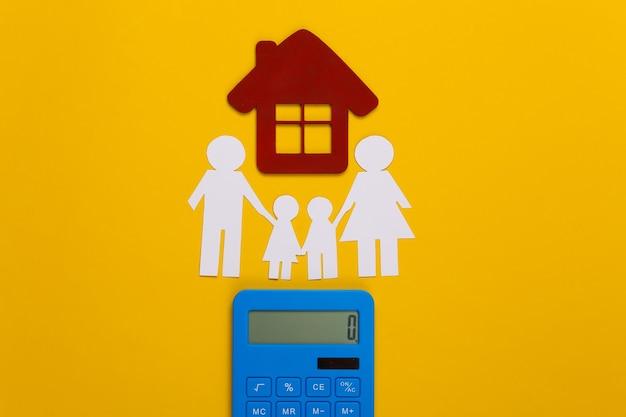 Famiglia felice di carta insieme alla casa, calcolatrice su giallo. calcolo delle spese familiari, budget