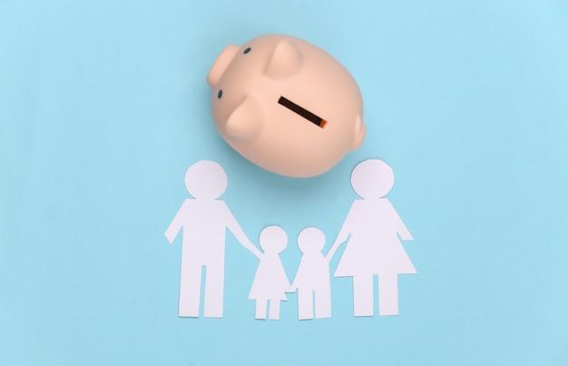 Famiglia felice di carta insieme al porcellino salvadanaio sull'azzurro. bilancio familiare