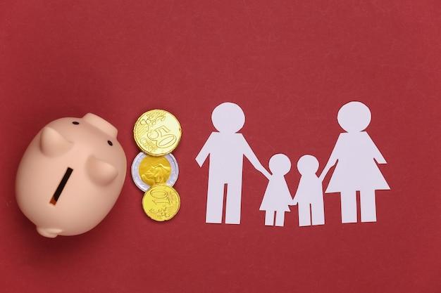 Famiglia felice di carta insieme a salvadanaio e monete su rosso. bilancio familiare