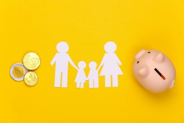 Famiglia felice di carta insieme al salvadanaio, monete su giallo. bilancio familiare