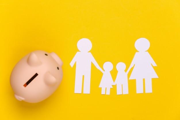 Famiglia felice di carta insieme al salvadanaio su giallo. bilancio familiare