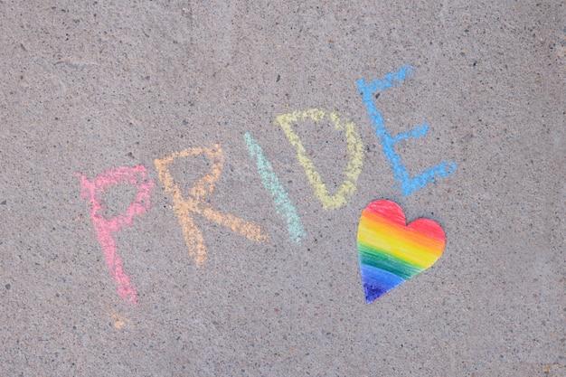 Cuore di carta dipinto nei colori dell'arcobaleno iscrizione di orgoglio della comunità lgbt in gesso su asfalto, concetto di mese dell'orgoglio arte temporanea