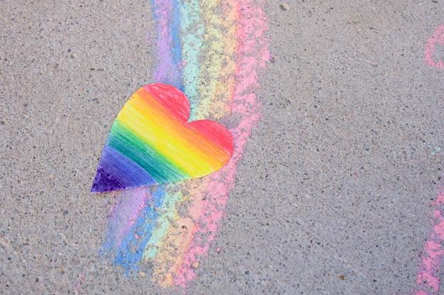 Cuore di carta dipinto con i colori dell'arcobaleno della comunità lgbt e un arcobaleno disegnato con il gesso sul marciapiede, concetto del mese dell'orgoglio, relazioni omosessuali
