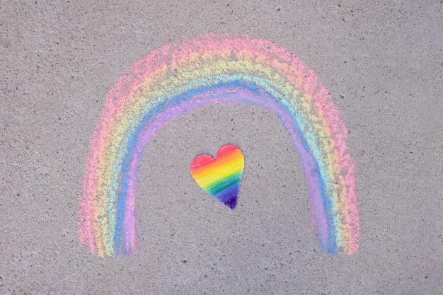 Cuore di carta dipinto con i colori dell'arcobaleno della comunità lgbt e arcobaleno dipinto con il gesso su asfalto, concetto del mese dell'orgoglio
