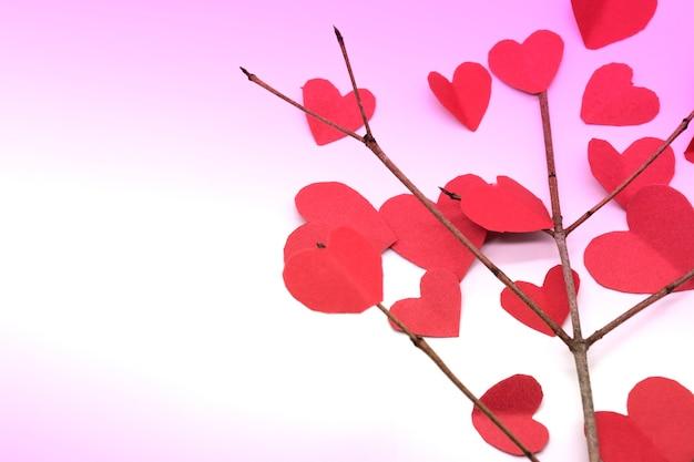 Cuori di carta sui rami degli alberi isolati su bianco con sfondo rosa per san valentino