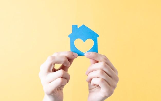 Casa di carta in mani femminili su sfondo giallo