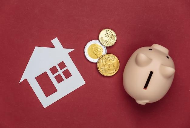 Casa di carta e salvadanaio con monete su un rosso.