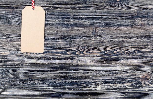 Etichetta di carta contro una superficie piana di legno nera, primo piano del settore dello sconto