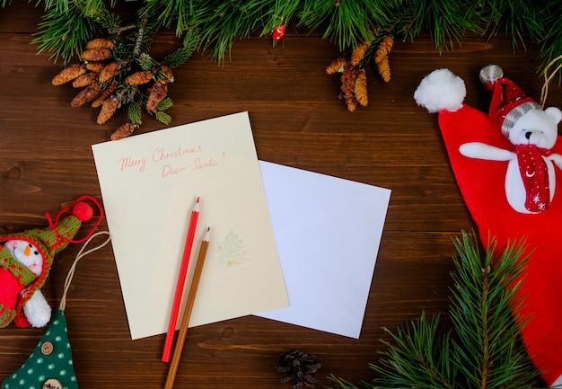 Lettera di carta a babbo natale su un tavolo di legno con giocattoli, rami di pino, matite pigne e