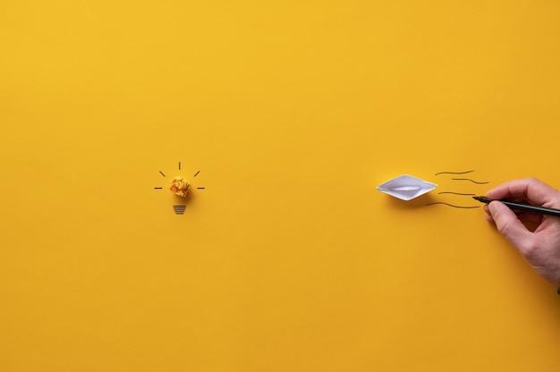 Barca origami fatta di carta che galleggia verso una lampadina di carta gialla in un'immagine concettuale di visione e idea.