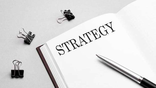 Nota cartacea con testo strategia, penna e strumenti per ufficio