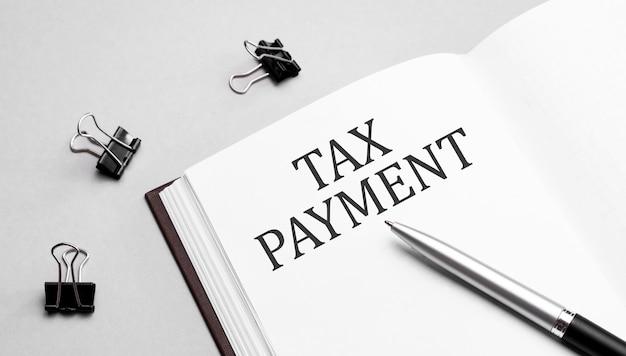 Nota di carta con testo pagamento fiscale, penna e strumenti per ufficio, sfondo bianco. concetto di affari