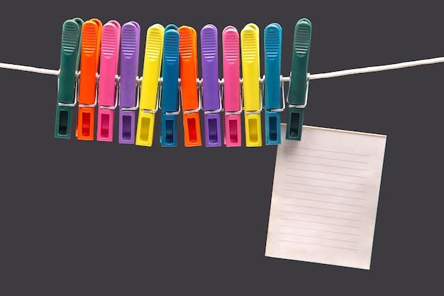 Blocco note di carta per promemoria appeso a mollette colorate
