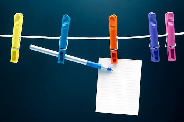 Blocco note di carta per promemoria e penna appesa a mollette colorate