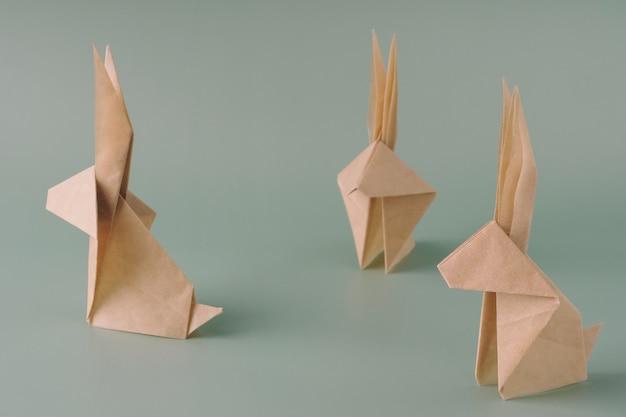 Coniglietto di carta origami su sfondo blu pastello. mestieri di carta. il concetto minimale di pasqua o l'anno del coniglio. coniglietto di pasqua.