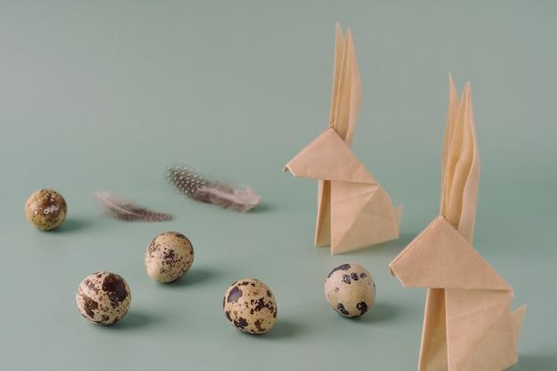 Coniglietto di carta origami, uova di quaglia su sfondo blu pastello. concetto di pasqua moderno minimale. sfondo luminoso di pasqua.