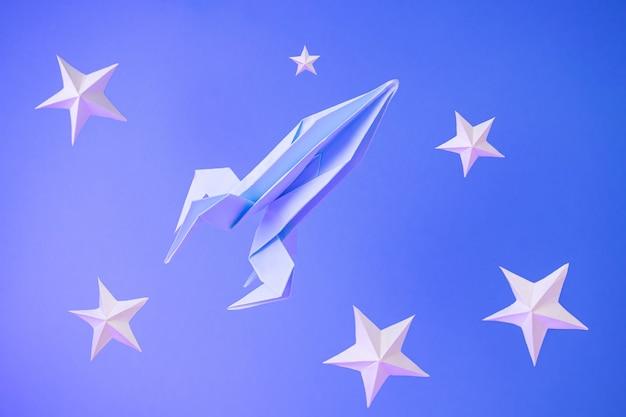Il razzo di carta origami vola tra le stelle di carta su un blu